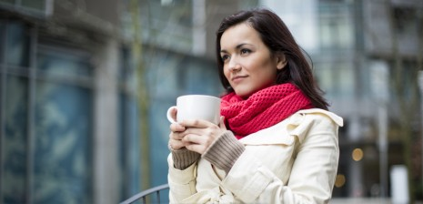 A woman sipping on a cup of coffee.